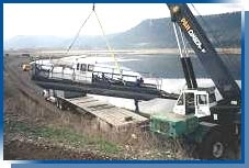 Dredging machine being lowered into a pond with a crane